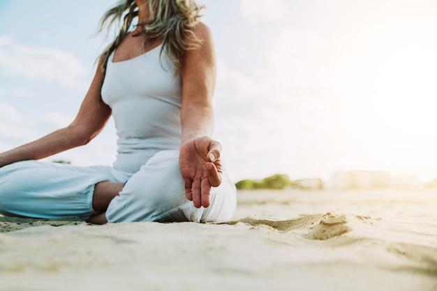 Senior vrouw in lotus houding zittend op het zand yoga op het strand