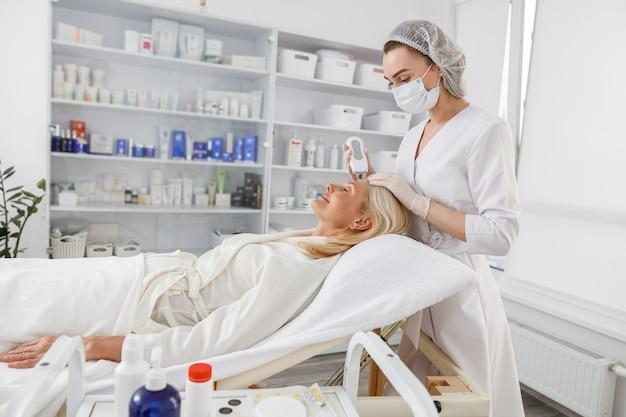 Senior vrouw in professionele beauty spa salon tijdens ultrasone gezichtsreinigingsprocedure.