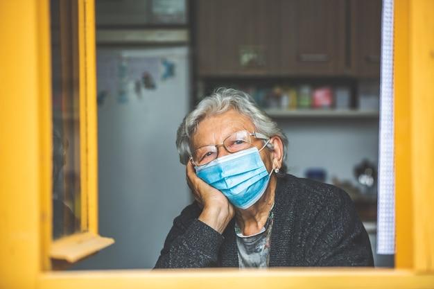 Senior vrouw in quarantaine geplaatst door coronavirus, covid-2019 bij een huis, naar buiten kijkend bij het raam
