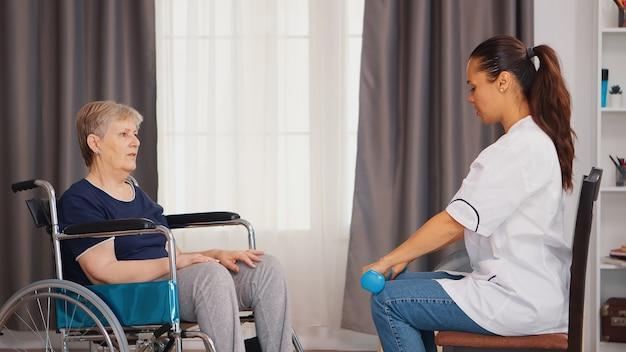 Senior vrouw in rolstoel die fysieke revalidatie doet met een arts. training, sport, herstel en tillen, bejaardentehuis, zorgverpleging, gezondheidsondersteuning, sociale bijstand, doc