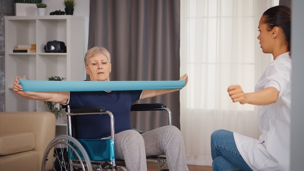 Senior vrouw in rolstoel die revalidatiebehandeling doet met hulp van verpleegkundige. training, sport, herstel en tillen, bejaardentehuis, zorgverpleging, gezondheidsondersteuning, sociale hulp