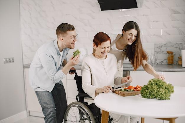 Senior vrouw in rolstoel koken in de keuken. mensen met een handicap echtpaar helpt haar.