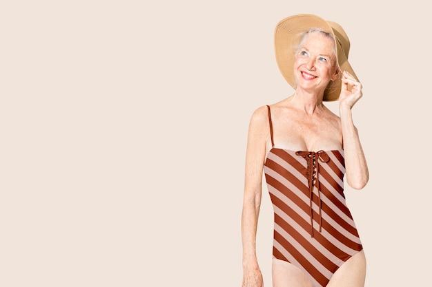 Senior vrouw in rood gestreepte zomerkleding uit één stuk met ontwerpruimte