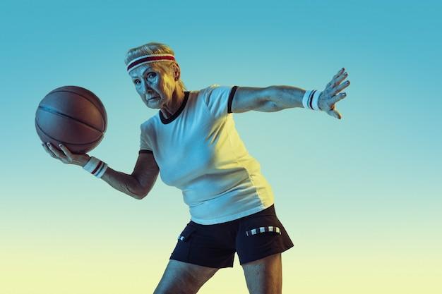 Senior vrouw in sportwear basketbal spelen op verloop achtergrond, neon licht. vrouwelijk model in uitstekende conditie blijft actief. concept van sport, activiteit, beweging, welzijn, vertrouwen. copyspace.