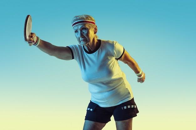Senior vrouw in sportwear training in tafeltennis op achtergrond met kleurovergang, neonlicht. vrouwelijk model in uitstekende conditie blijft actief. concept van sport, activiteit, beweging, welzijn, vertrouwen. copyspace.