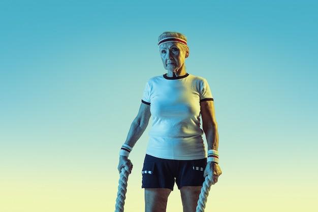 Senior vrouw in sportwear training met touwen op de achtergrond met kleurovergang, neonlicht. vrouwelijk model in uitstekende conditie blijft actief. concept van sport, activiteit, beweging, welzijn, vertrouwen. copyspace.