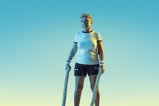 Senior vrouw in sportwear training met touwen op de achtergrond met kleurovergang, neonlicht.