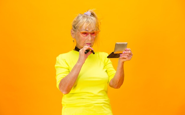 Senior vrouw in ultra trendy kleding geïsoleerd op fel oranje