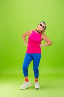 Senior vrouw in ultra trendy kleding geïsoleerd op felgroene achtergrond