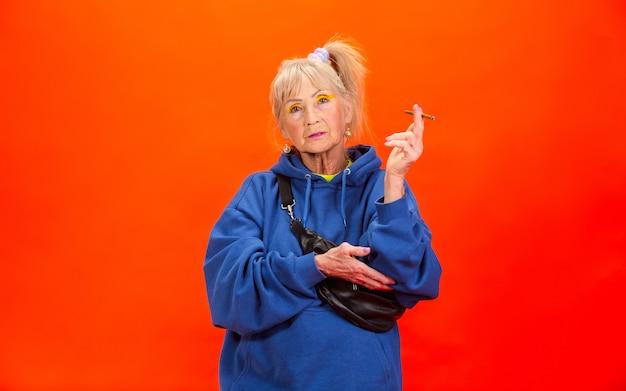 Senior vrouw in ultra trendy kleding geïsoleerd op oranje