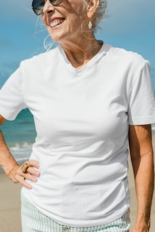 Senior vrouw in wit t-shirt op het strand