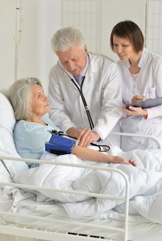 Senior vrouw in ziekenhuis met zorgzame artsen