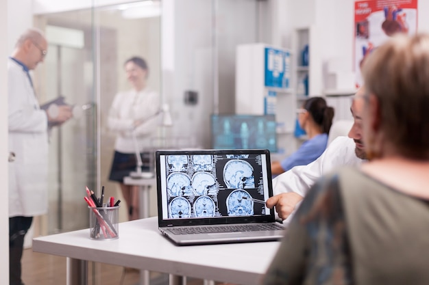 Senior vrouw in ziekenhuiskantoor kijkt naar hersen-ct-scan terwijl ze met de arts praat over de diagnose. zieke jonge vrouw en bejaarde dokter met grijs haar in de gang van de kliniek.