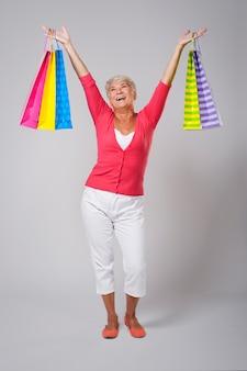 Senior vrouw is erg blij met winkelen