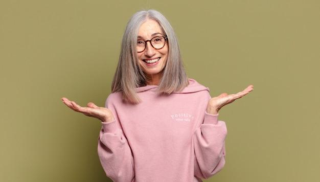 Senior vrouw kijkt blij en opgewonden, geschokt door een onverwachte verrassing met beide handen open naast gezicht