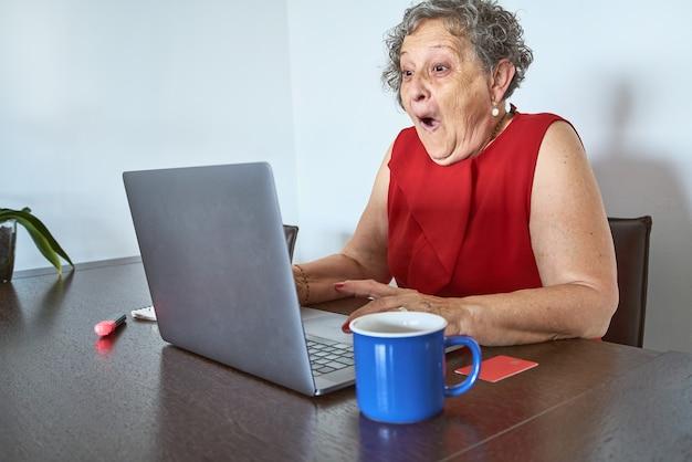 Senior vrouw kijkt erg verrast naar het scherm van de laptop