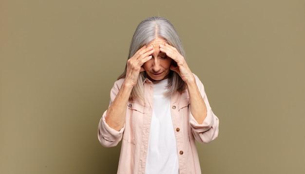 Senior vrouw kijkt gestrest en gefrustreerd, werkt onder druk met hoofdpijn en heeft problemen