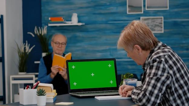 Senior vrouw kijkt naar een groen scherm dat vanuit huis werkt en maakt aantekeningen op een notebook voor oudere zaken...