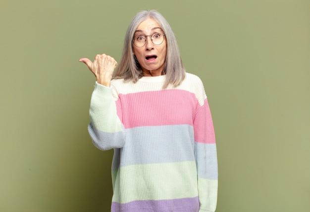 Senior vrouw kijkt verbaasd in ongeloof, wijst naar een object aan de zijkant en zegt wow, ongelooflijk