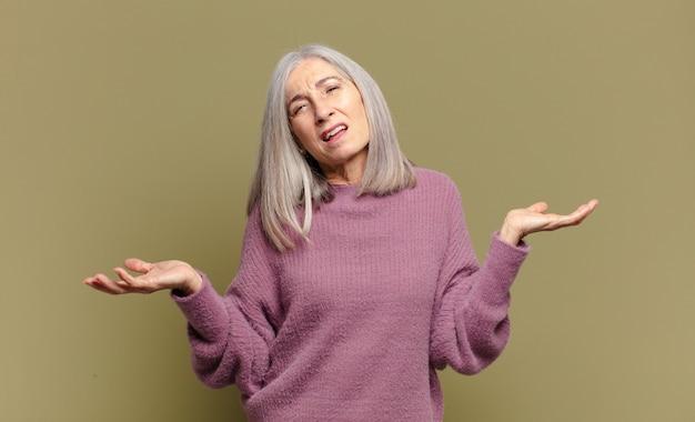 Senior vrouw kijkt verbaasd, verward en gestrest, vraagt zich af tussen verschillende opties, voelt zich onzeker