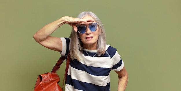 Senior vrouw kijkt verbijsterd en verbaasd, met hand over voorhoofd ver weg kijkend