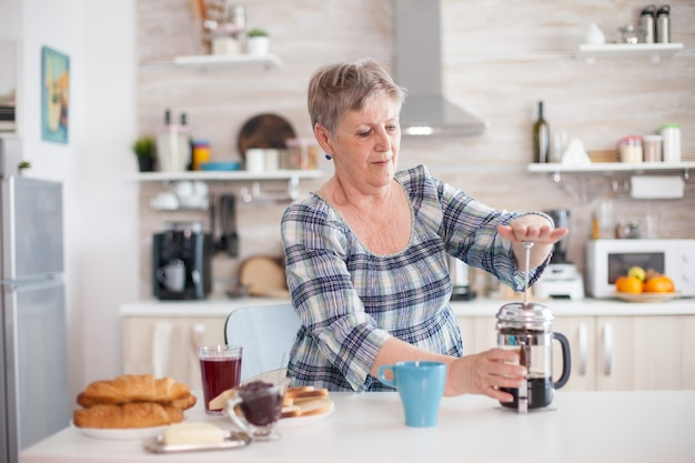 Senior vrouw koffie maken met franse pers in de keuken tijdens het ontbijt. bejaarde in de ochtend genietend van vers bruin café espressokopje cafeïne uit vintage mok, filter ontspannen verfrissing
