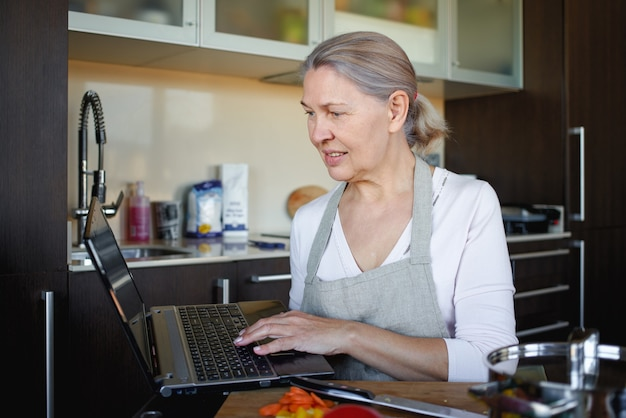 Senior vrouw koken met behulp van recept op laptop.
