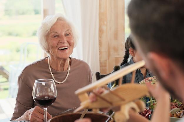 Senior vrouw lachend terwijl ze aan tafel zit ze blij voor haar zoon en zijn gezin