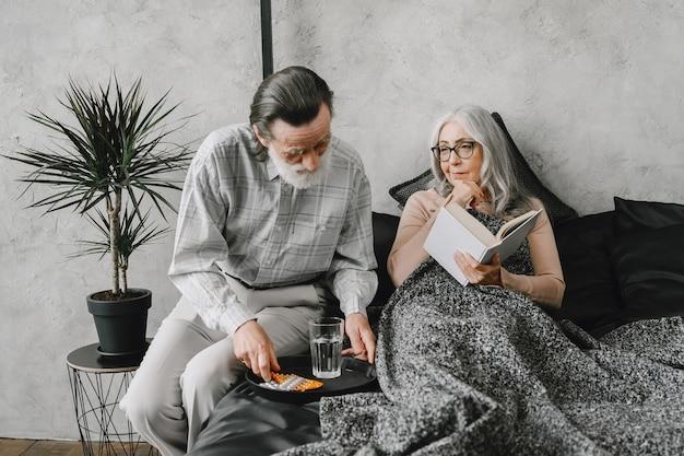 Senior vrouw liggend op bed en het nemen van pillen met zorgzame echtgenoot. ziekte, quarantaine.