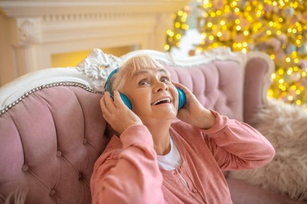 Senior vrouw luisteren naar muziek in koptelefoon