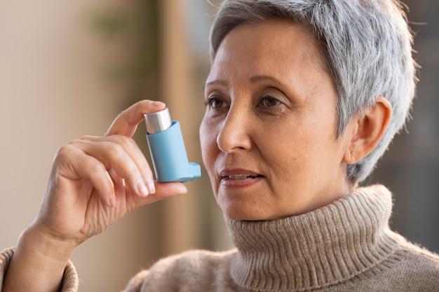 Senior vrouw met astma-inhalator