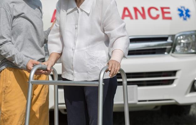 Senior vrouw met behulp van een rollator met verzorger om ambulance te nemen