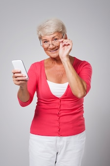 Senior vrouw met behulp van hedendaagse smartphone
