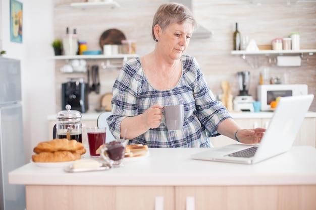 Senior vrouw met behulp van laptop in de keuken tijdens het ontbijt en het drinken van koffie. oudere gepensioneerde die vanuit huis werkt, telewerken met behulp van externe internetbaan online communicatie over moderne technologie nee
