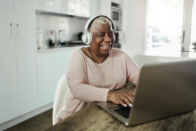Senior vrouw met behulp van laptop terwijl het dragen van een koptelefoon thuis - joyful ouderen levensstijl en technologie concept - focus op gezicht Premium Foto