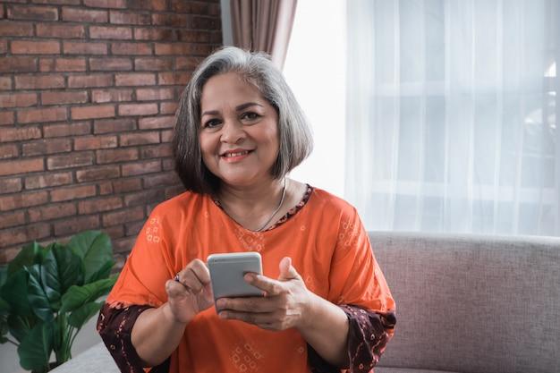 Senior vrouw met behulp van mobiele telefoon