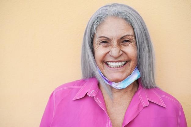 Senior vrouw met beschermend masker onder kin tijdens uitbraak van coronavirus