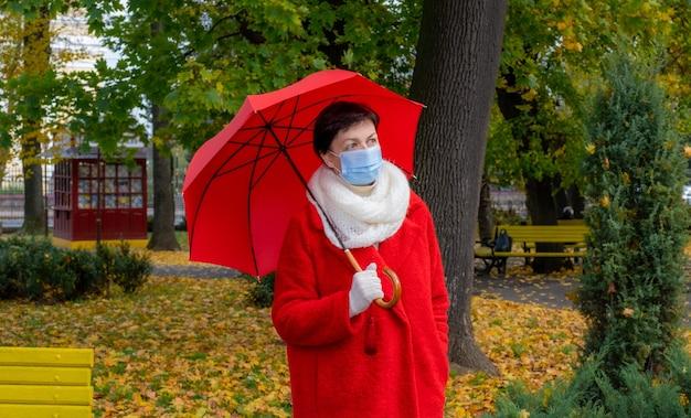 Senior vrouw met beschermend medisch masker op haar gezicht loopt in herfst park met rode paraplu.