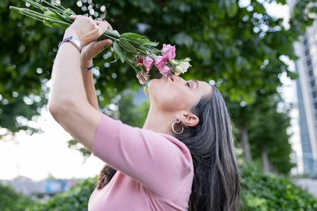 Senior vrouw met bloemen in het park