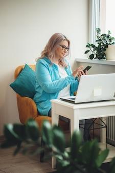 Senior vrouw met blond haar en bril die aan telefoon en laptop thuis werkt tijdens de quarantaine
