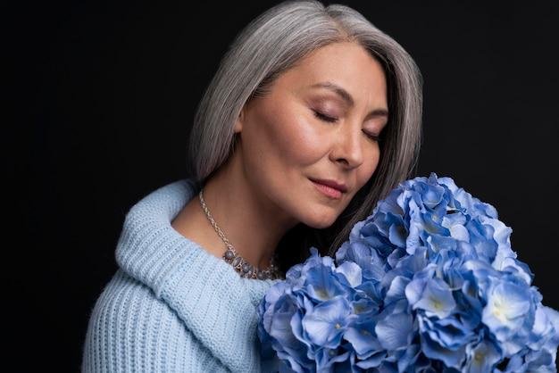Senior vrouw met boeket bloemen portret