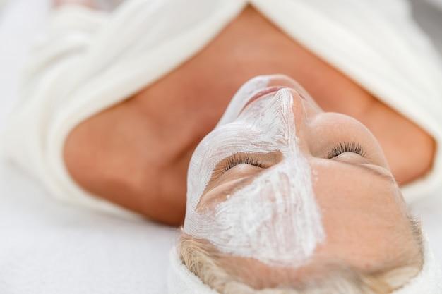 Senior vrouw met cosmetisch masker op half gezicht bij schoonheidssalon die op coach legt.