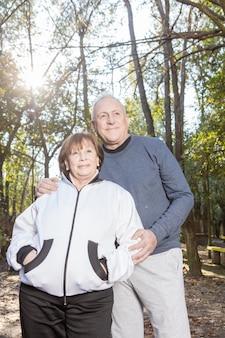 Senior vrouw met de handen in de zakken poseren met haar echtgenoot