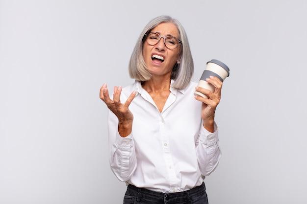 Senior vrouw met een afhaalkoffie