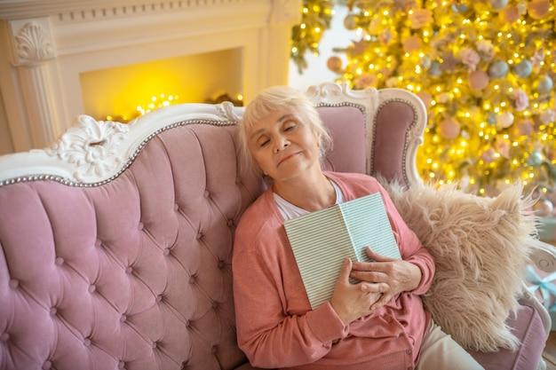 Senior vrouw met een boek en dutten op de bank