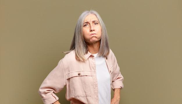 Senior vrouw met een gekke, gekke, verbaasde uitdrukking, puffende wangen, zich gevuld, dik en vol eten