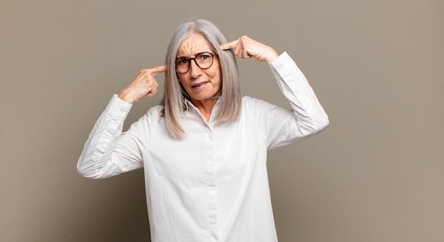 Senior vrouw met een serieuze en geconcentreerde blik, brainstormend en nadenkend over een uitdagend probleem