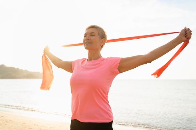 Senior vrouw met elastische kabel op het strand