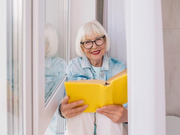 Senior vrouw met grijs haar leest een boek bij het raam thuis onderwijs pensioen anti leeftijd