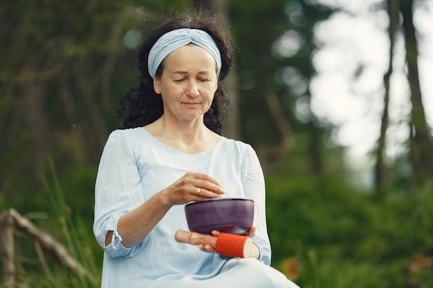 Senior vrouw met hindoeïstische dingen. dame in een blauwe jurk. brunette zittend.